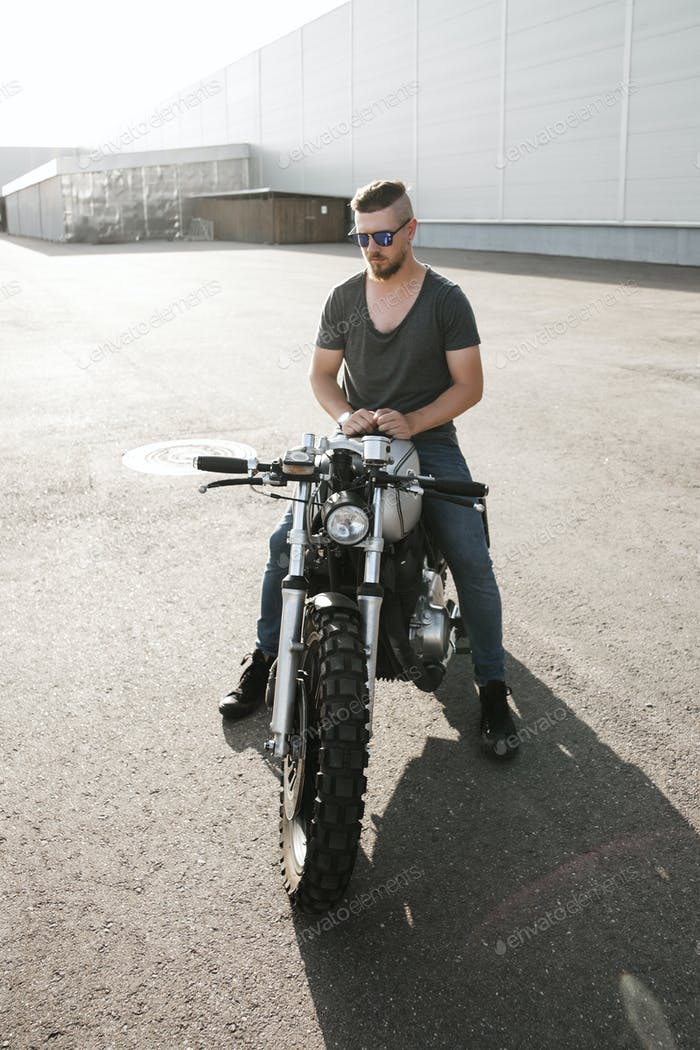 Rider guy with classic style cafe racer motorcycle