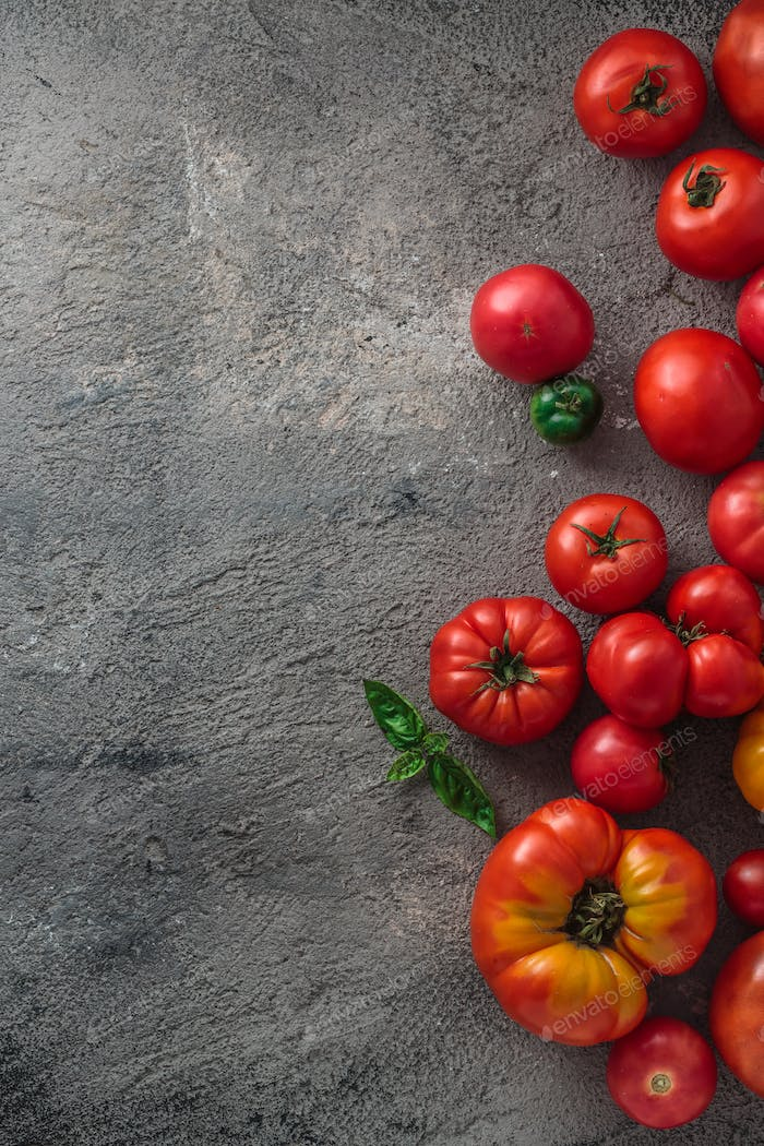 Fresh tomatoes on a concrete background. Top view with copy space