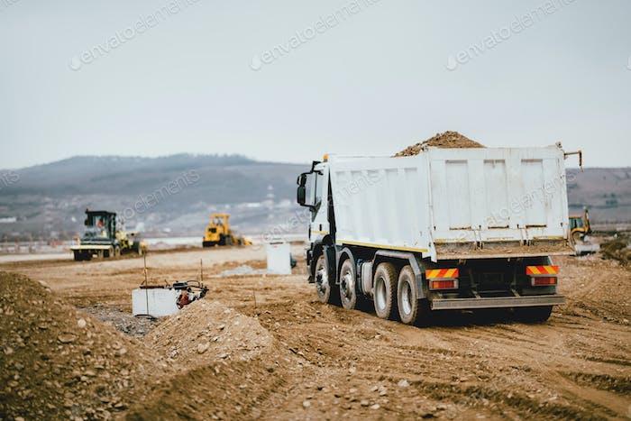 Industrial dumper trucks working on highway construction site,