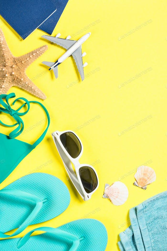 Blaue Flip-Flops, Sonnenbrille, Reisepass, Flugzeug und Seestern auf gelbem Hintergrund