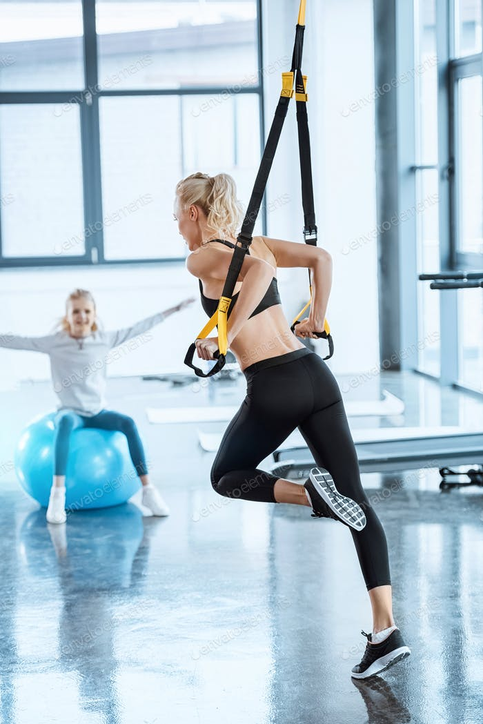 Blonde fitness woman training with trx fitness straps