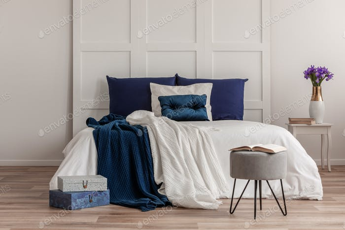 Open book on grey pouf in front of king size bed with white and blue bedding