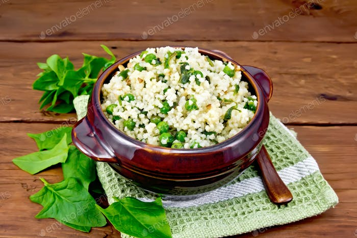 Couscous with spinach and green peas in bowl on board