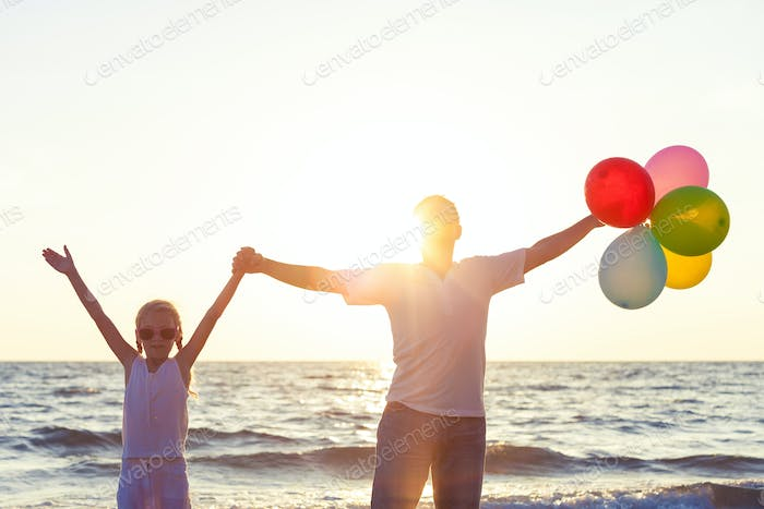 Father and daughter with balloons playing on the beach at the su