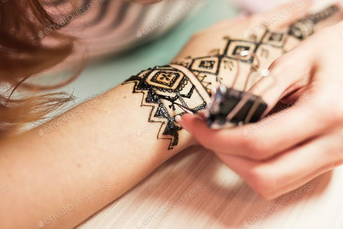 Drawing process of henna menhdi ornament on woman's hand.