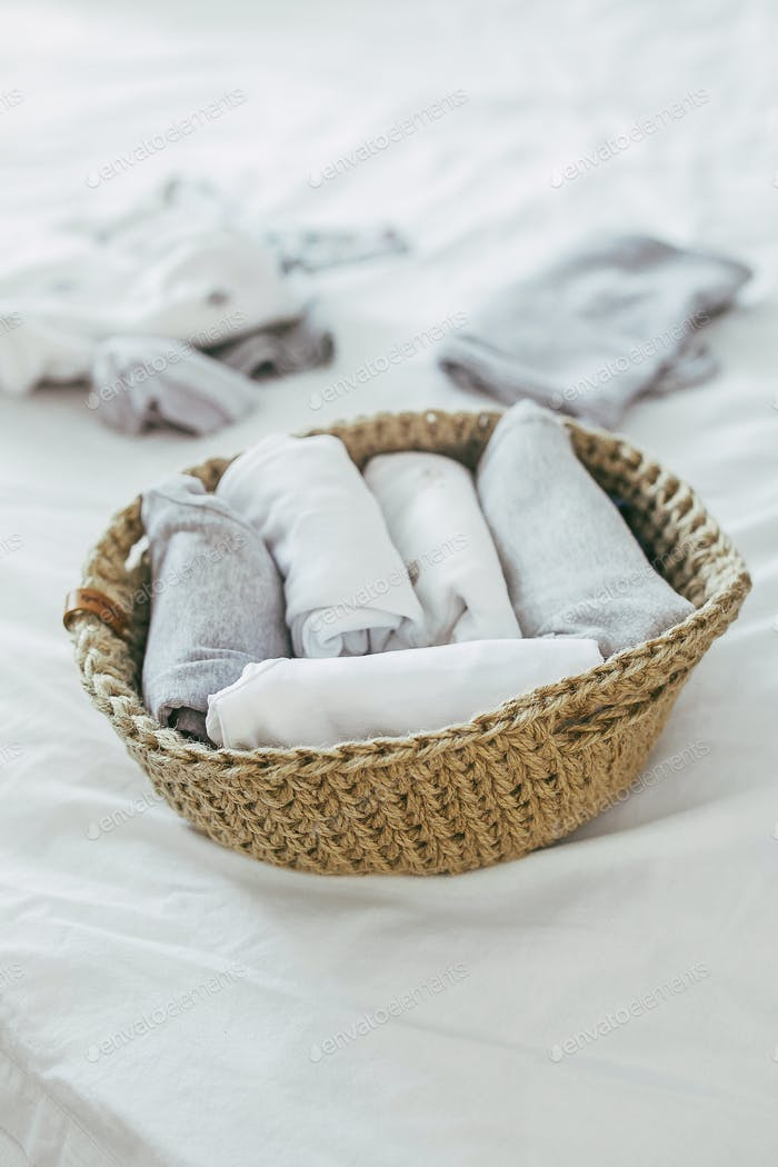 Folding clothes in jute basket in the konmari system. Concept of organizing minimalism clothes