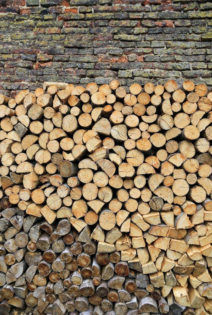 Stack of firewood on a old weathered brick wall background