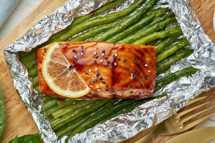 Folienpackung Abendessen mit rotem Fisch. Lachsfilet mit Spargel. Ofen gebackenes warmes Abendessen