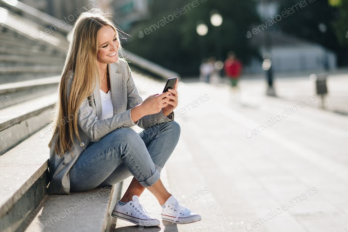 Beautiful young blonde woman looking at her smartphone and smili