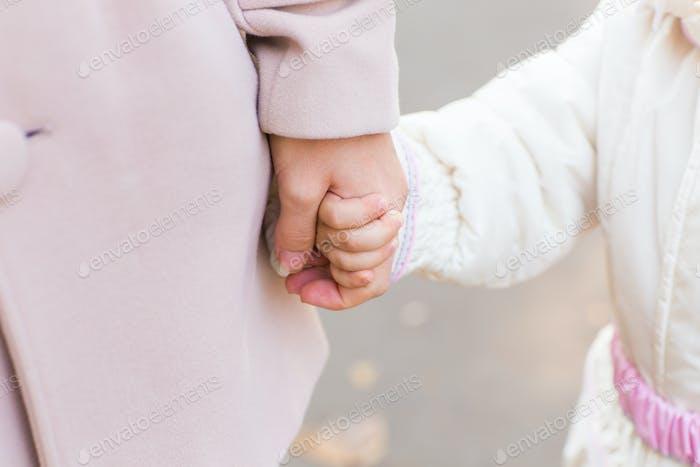 Kind hält die Hand der Mutter