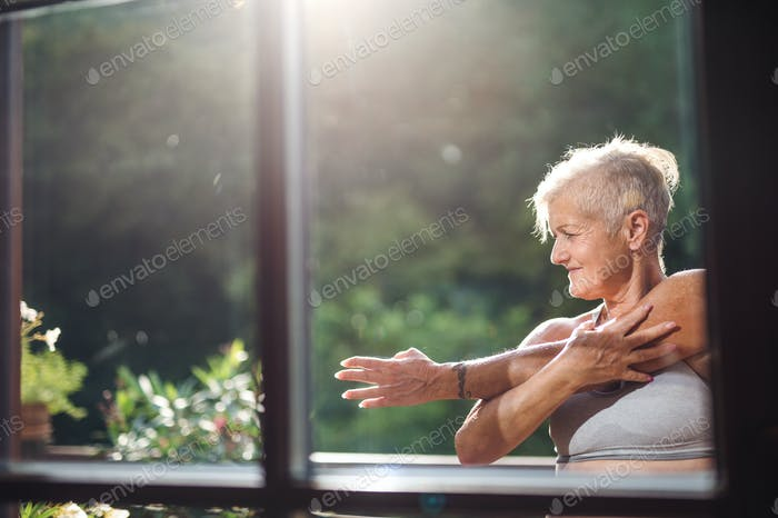 A senior woman with sports bra stretching outdoors on a terrace in summer.