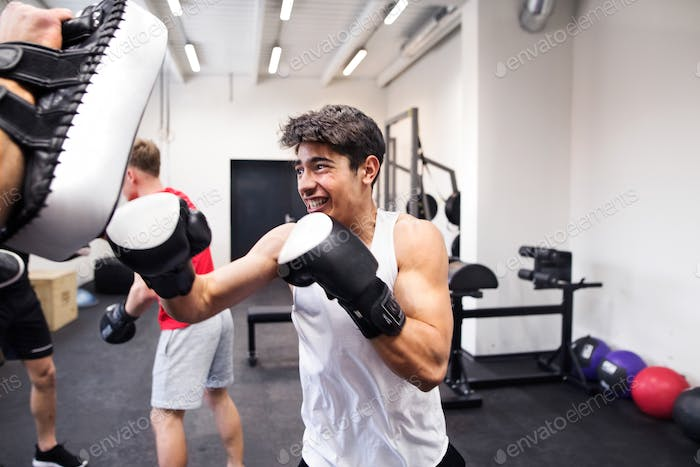 Fit hispanic man in gym boxing with his trainer