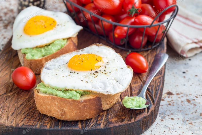 Open sandwiches with mashed avocado and fried egg, horizontal, copy space