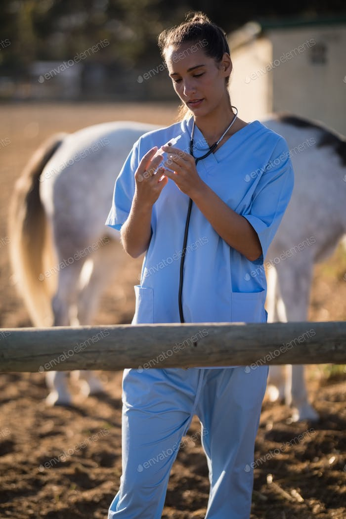 Female vet examining syringe at barn