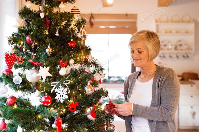 Senior Frau zu Hause Dekoration Weihnachtsbaum.