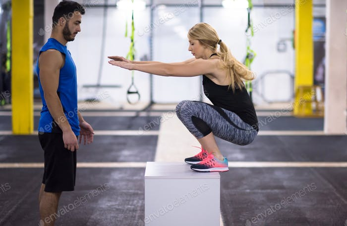 woman working out with personal trainer jumping on fit box