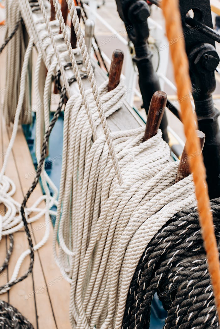 Old sailboat, closeup of wooden cleats with nautical moored ropes.