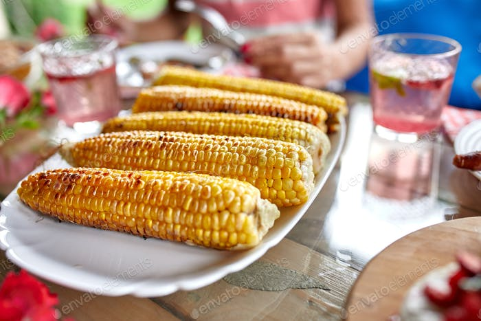 Grilled corn cobs on plate on the dinner table, appetizers