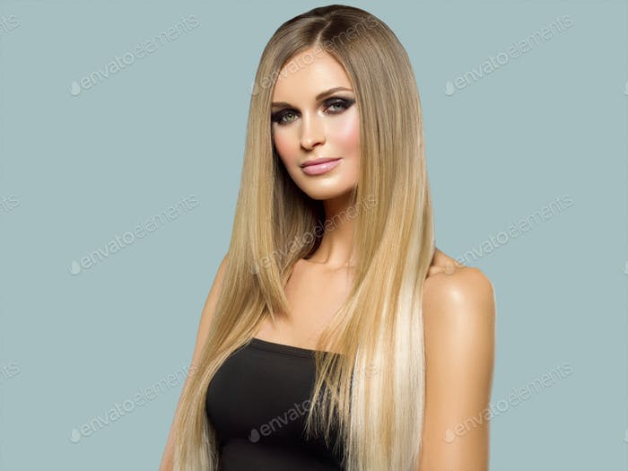 Woman smooth hair blonde lond beauty natural casual portrait. On gray.