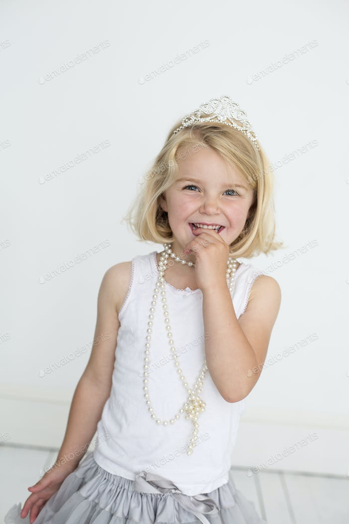 Young girl wearing a tiara and a pearl necklace, posing for a picture in a photographers studio.