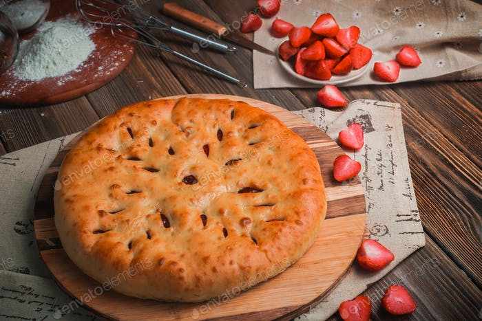 Homemade strawberry pie on a wooden kitchen table with ingredients. Traditional baking header