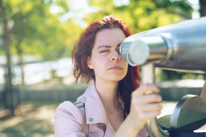 Young girl looking through a telescope outdoors
