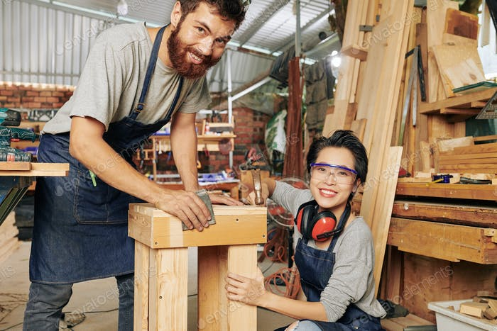 Cheerful carpenters making furniture