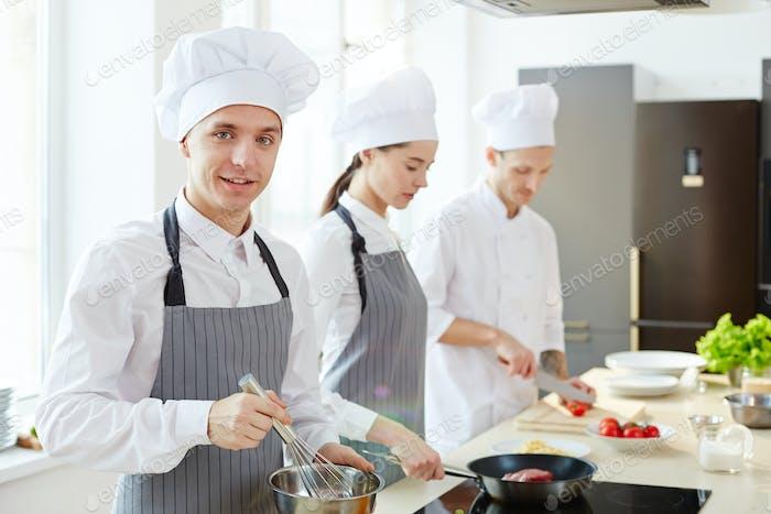 Lächelnder junger Koch in Schürze und Hut