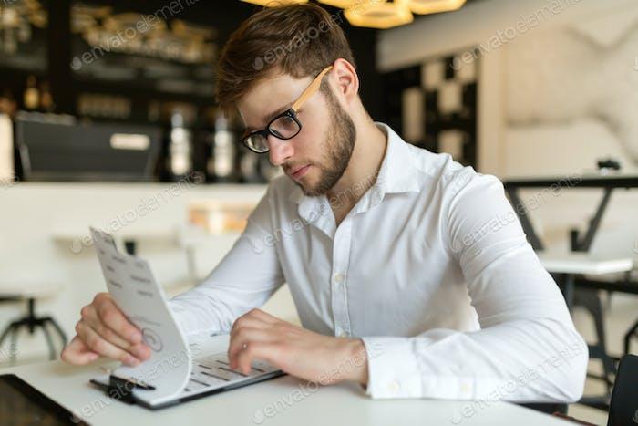 Businessman choosing from menu in restaurant