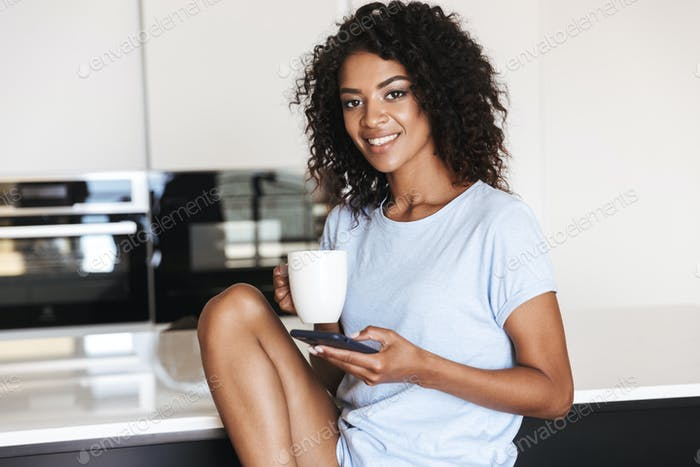 Satisfied african woman using mobile phone