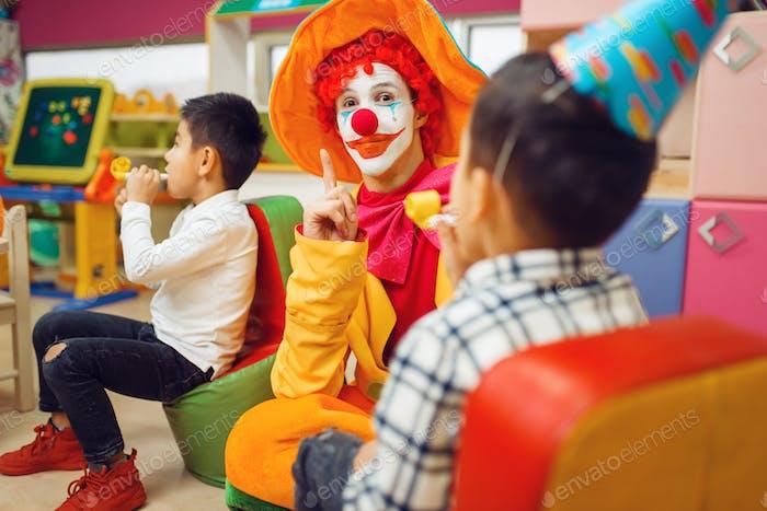Lustiges Clown-Spiel mit fröhlichen Kindern zusammen