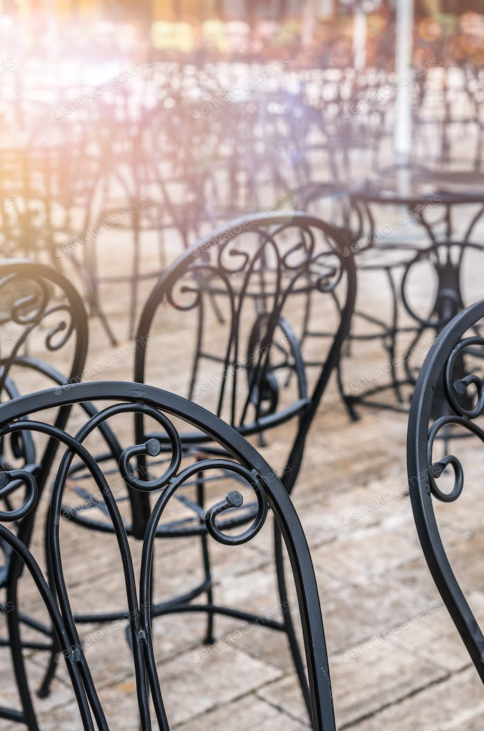 Black empty metal chairs outside a restaurant