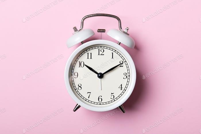 White vintage alarm clock on pink background