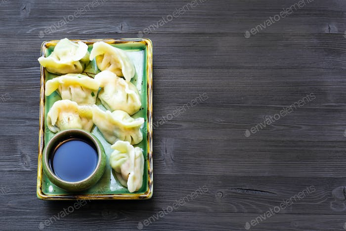 Dumplings on plate on dark table with copyspace