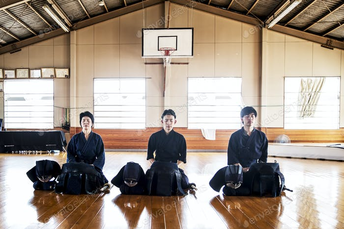Female and two male Japanese Kendo fighters kneeling on wooden floor, meditating.