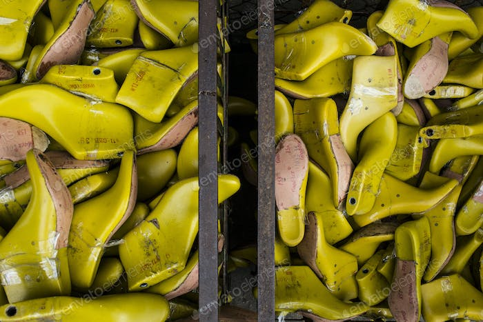 High angle close up of bins of yellow shoe molds in a factory.