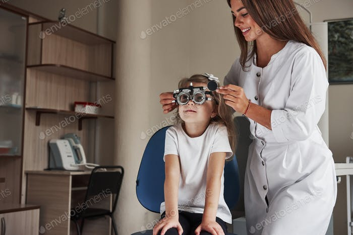 Work in progress. Little girl in glasses sitting in clinic and having her eyes tested
