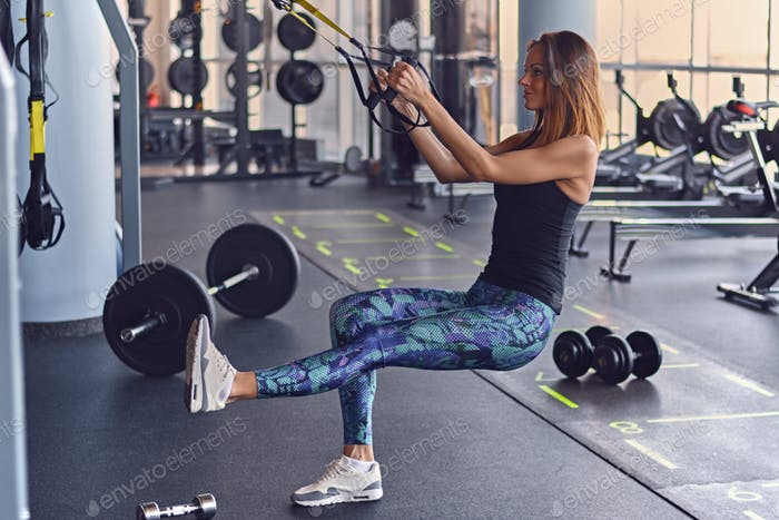 Sporty female exercising with trx suspension strips in a gym club.