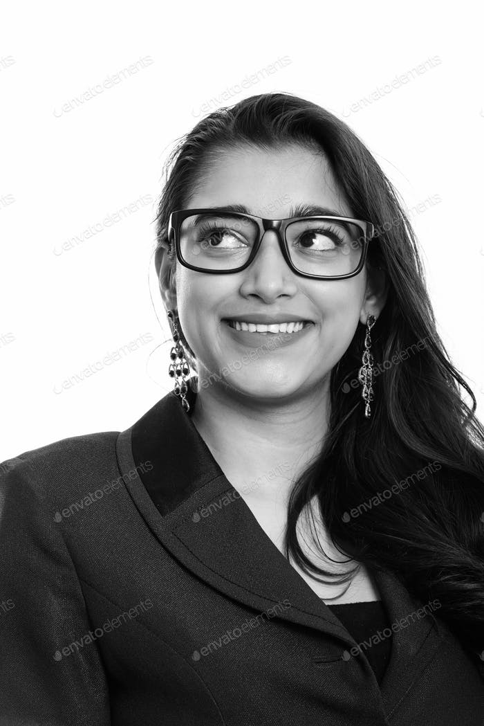 Young happy Indian businesswoman smiling while thinking and looking up
