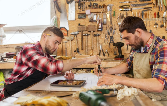 Arbeiter mit Bauplan und Trennwänden in der Werkstatt