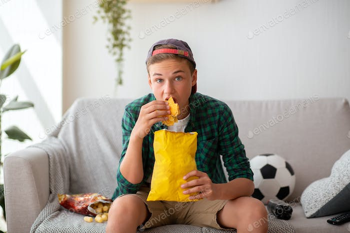 Teenager watching football game and eating unhealthy food