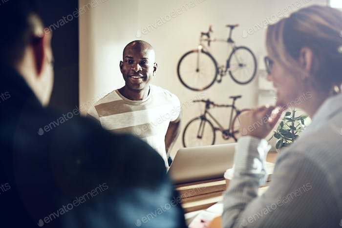 Smiling African man talking with colleagues around an office table