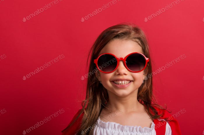 Portrait of a small girl with red sunglasses in studio on a red background.