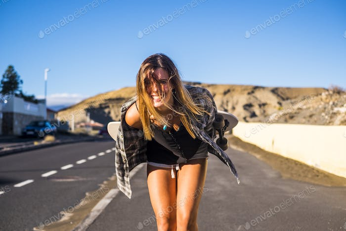 nice girl with big smile on the road with skateboard