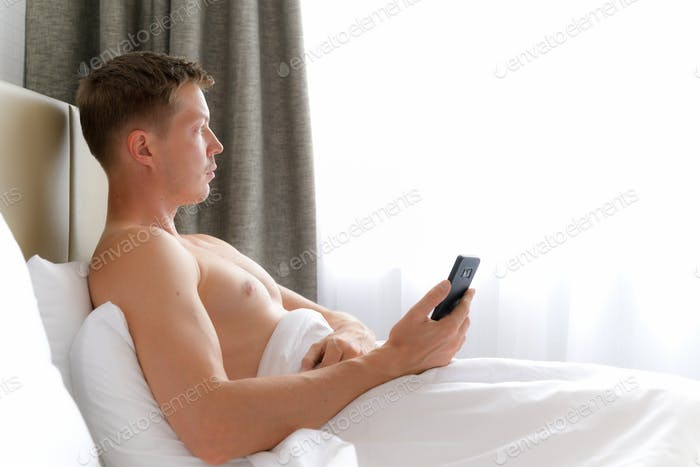 Man Using Mobile Phone In Bed And Looking Through Window