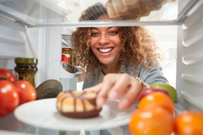 Blick aus dem Inneren des Kühlschranks als Frau öffnet Tür und reicht für ungesunde Donut