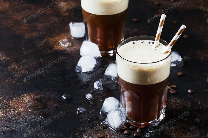 Cold frappe coffee with ice and foam in large glasses on brown background