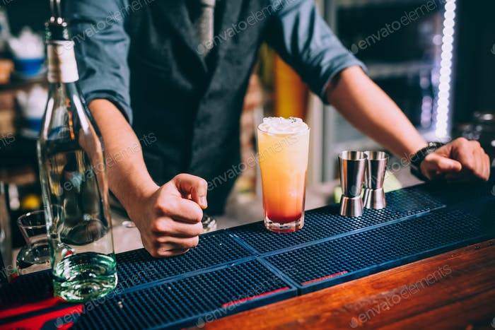 Portrait of elegant and vintage bartender, barman preparing orange based vodka and tequila cocktails
