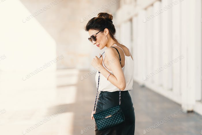 Beautiful smiling young woman in sunglasses looking away over the shoulder