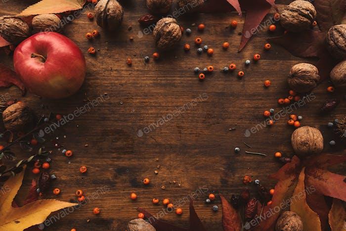 Herbstfrüchte, Beeren und Blätter auf hölzernem Hintergrund
